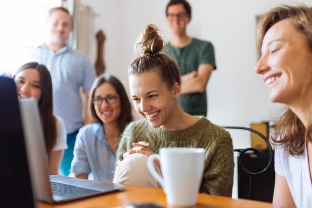Ľudia sedia okolo notebooku sledujú ho a smejú sa